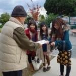笑顔で「介護の日」を紹介するチラシを渡す専攻科の学生たち(宇多津町臨海公園)