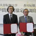 交流協定書に署名した田中学長(左)と石川学長