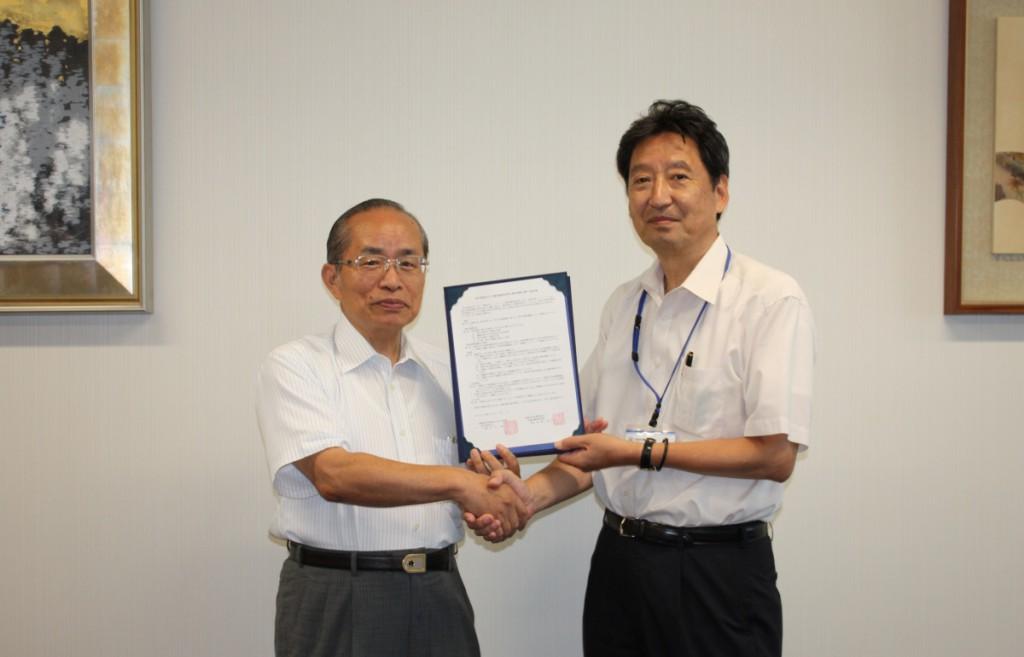 石川浩学長(左)と金﨑正久校長(右)が協定書の交換