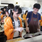 調理&商品開発ゼミのゼミ生が朝早くから300食ものうどんトッピングの仕込みや調理を行い、学生食堂で仕上げを行った後、来場者に3種類のうどんが振る舞われました