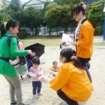 家族連れに手づくりフロランタンを奨める学生たち(うたづ臨海公園)