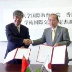 協定書に調印し、末永い交流を誓って握手を交わす周学院長(左)と石川学長
