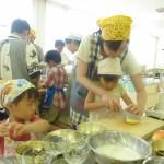 学生の手助けで調理する子供たち