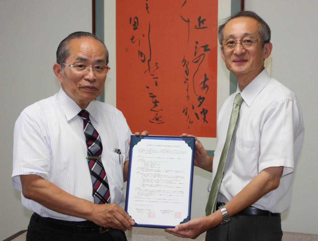 石川浩学長(左)と丸谷幸彦校長(右)が協定書の交換